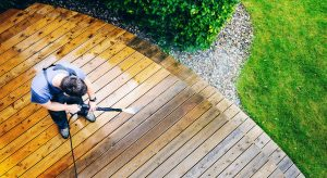 man cleaning deck with a pressure washer
